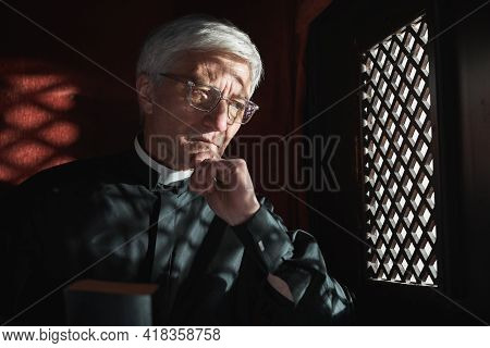 Senior Priest Sitting Behind The Grid And Listening The Confession In The Church