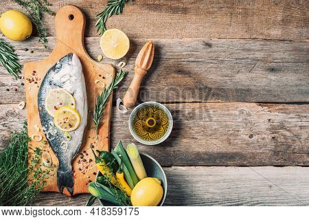Raw Dorado Fish With Ingredients, Lemon, Herbs, Oil, Vegetables And Spices Over Wooden Cutting Board