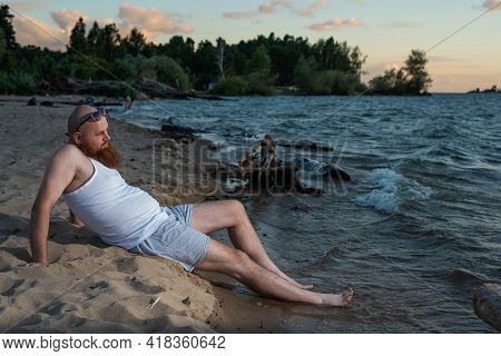 Funny Bald Man With Red Beard Dressed In Underwear Posing On The Beach. A Humorous Male Parody Of A