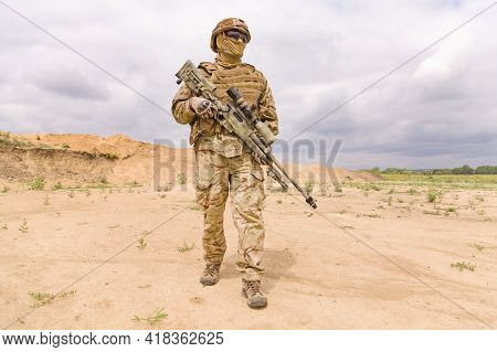 Fully Equipped And Armed Soldier With Rifle In The Desert. Concept Of Military Anti-terrorism Operat