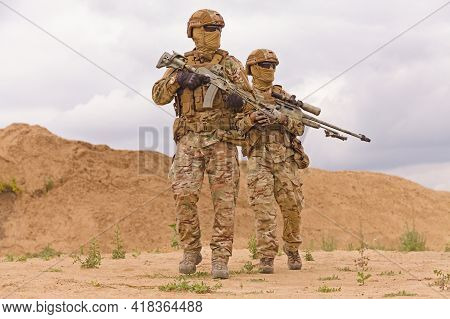 Equipped And Armed Special Forces Soldiers In The Desert. Concept Of Military Operations.