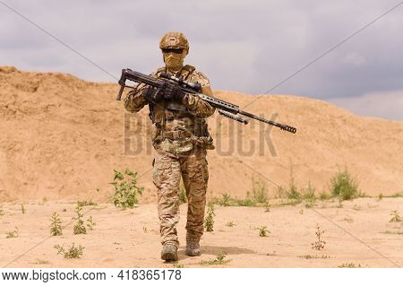 Armed Special Forces Soldier With Rifle In The Desert During The Military Operation. Concept Of Mili