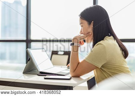 Thoughtful Woman Working On Tablet Computer At Home