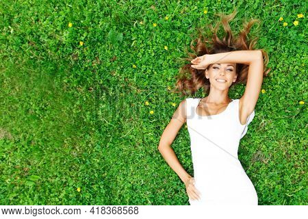 Pretty woman in white laying on the grass top view