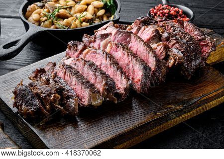 Sliced Grilled Meat Steak Rib Eye Medium Rare Set, On Wooden Serving Board, With White Beans And Ros