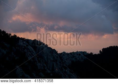 Majestic View On Sky And Clouds At Sunrise. Dark Silhouettes Of Mountains At Dawn.