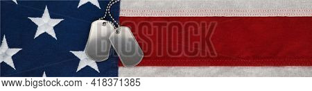 US military soldier's dog tags, rough and worn with blank space for text, on the American flag. Memorial Day or Veterans Day concept.