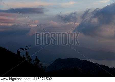 Majestic Sky With Vivid Clouds. Dark Silhouettes Of Mountains And Trees At Dawn.
