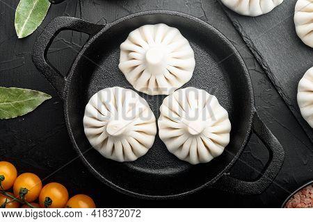 Manti, Turkish Traditional Ravioli Set, In Frying Cast Iron Pan, On Black Stone Background, Top View