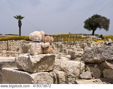 Two Teddy Bears Sitting On Ancient Rock At Archaeological Site