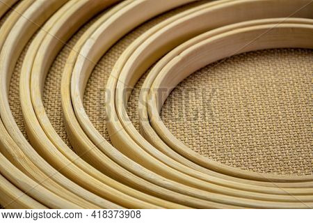 set of bamboo embroidery hoops against burlap canvas, craft and hobby concept