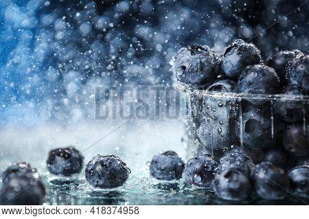 Blueberries In A Plastic Box Closeup Under The Water Drops In A Dark Blue Background. Healthy Lifest