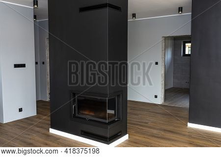 A Modern Standing Fireplace In The Living Room Enclosed With Panels, Painted Black With A Corner Pan