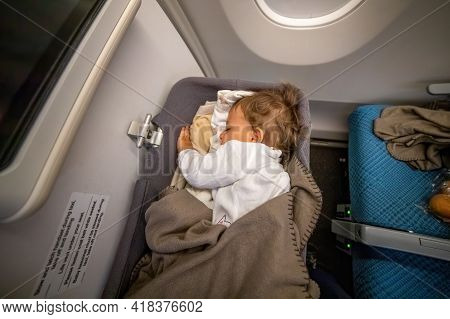 The Infant Passenger Safely And Comfortably Sleeps In The Baby Bussinet On A Long Flight