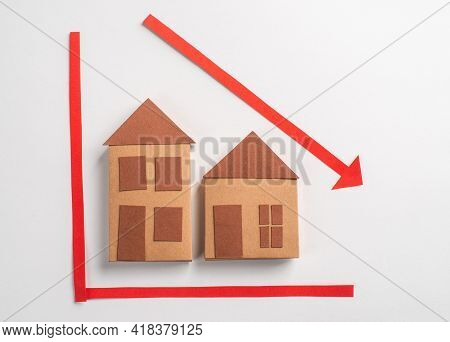 Paper House Toy On A Chart With Red Arrow Pointing Down
