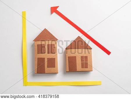 Paper Houses And Red Arrow Pointing Up On White Background