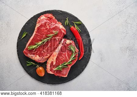 Two Raw Steak New York With Rosemary And Spices On Black Stone Cutting Board On Light White Stone Ba