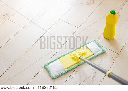 Microfiber Yellow Mop Isolated On White Wooden Floor Background, Closeup, Indoors. Chemical Bottle A