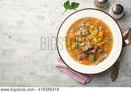 Beef And Barley Soup With Celery, Carrot And Onion In Plate On Concrete Background