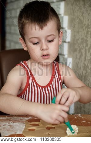 Little Boy Cutting Raw Dough In Flour With A Pizza Knife.