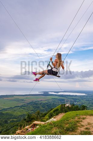 A Young Girl, Blonde, Swinging On A Swing On A Mountain Slope In Summer.