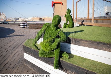 Male Figure Covered With Artificial Green Grass Sitting On Steps And Female Figure With Headphones I