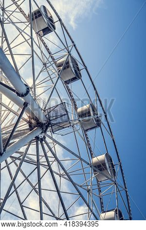 Gray Or White Metal Ferris Wheel With Closed Passenger Cabins Close-up In The Amusement Park In The