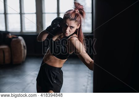 Athletic Fit Female Boxer Exercising Punches With Boxing Bag In Gym During Kickboxing And Self Defen