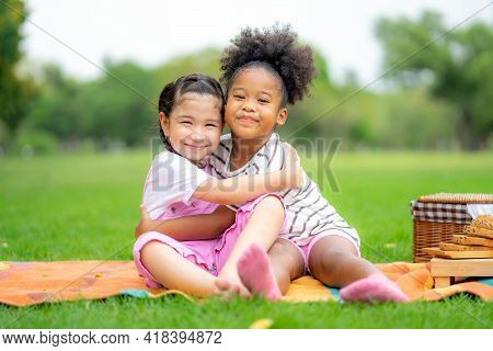 Two American African Little Girl As Friends Hug Each Other In Cheerful Way. Little Girlfriends In Pa