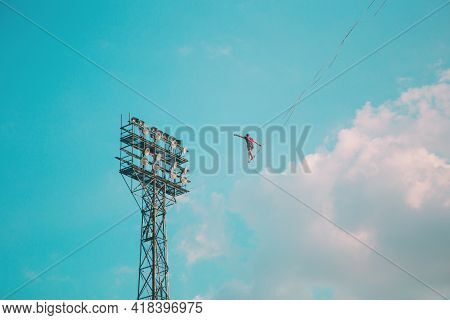 Highliner On A Background Of Blue Sky. A Man Walks Along A Sling Stretched Between The Towers. The P