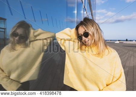 Portrait Of Young Beautiful Woman In Yellow Sweater And Sunglasses. Blonde Woman Standing Near Build