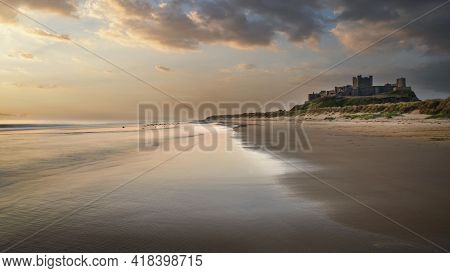 Stunning Epic Sunrise Landscape Over Beach With Medieval Castle Ruins In Background