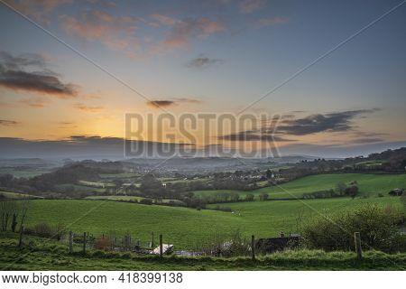 Beautiful Vibrant Sunrise Landscape Image Of Misty View Towards Symondsbury Village In Dorset On A S