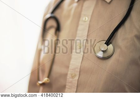 Doctor With A Stethoscope On Hospital Background. A Doctor In A White Coat With A Stethoscope. Coron