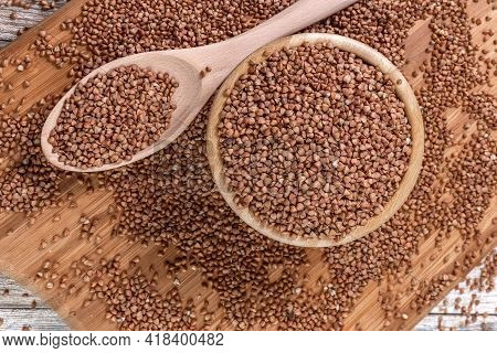 Cattered Buckwheat. Buckwheat In A Wooden Bowl And Spoon Lies On A Wooden Table. Scattered Buckwheat