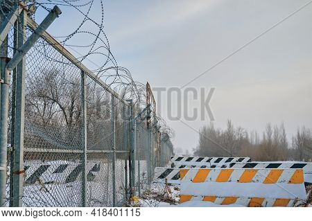 Barbed Wire Fence On Border In Winter. Closing For Quarantine. Private Object Near Highway. Concrete