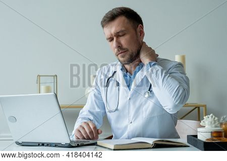 Man Doctor Is Stressed And Tired From Hard Work To Take Care Of Patients. Male Doctor Tired After Sh