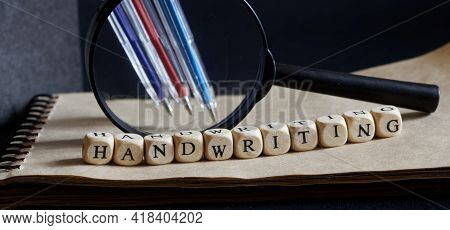 Magnifier, Ballpoint Pens, Notepad And The Inscription Handwriting On A Dark Background. Concept Of