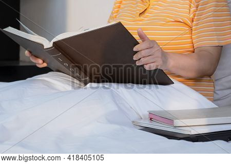Focus At Adult Fleshy Woman Hand Is Reading Textbook On Her Bed In Morning Time