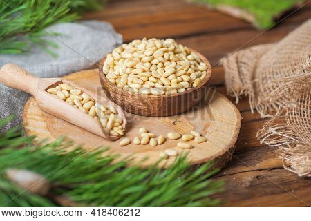 A Plate And A Scoop Filled With Pine Nuts Are On A Wooden Board On The Table. Nearby Are Pine Branch