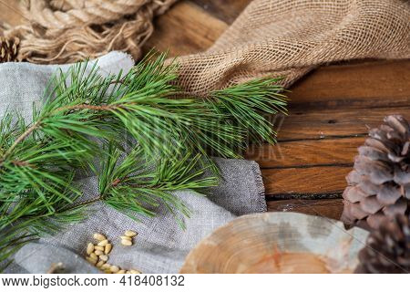 On A Wooden Table Lie Coarse Gray Fabrics, On Top Of A Green Pine Branch With Long Needles, A Handfu