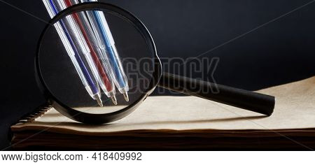 Magnifier, Ballpoint Pens And Notepad On A Dark Background. Concept Of Handwriting Expertise And For