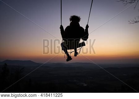 Hairy Young Boy Aged 16-20 Of European Descent Enjoys His Life Swinging On A Swing At Sunset On The