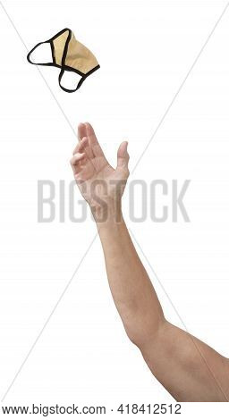A Hand Pitching A Used Covid Face Mask Away, Isolated On White With Copy Space.