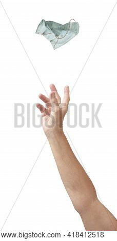 A Hand Throws A Filty Blue Face Mask Away, Isolated On White With Copy Space.