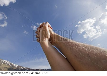Male And Female Hands Together Over Blue Sky