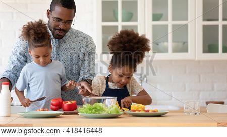 Happy African American Sibling Kids Helping Daddy To Prepare Dinner