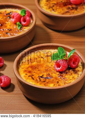 Creme Brulee Desserts With Cream And Cane Sugar With Fresh Raspberries And Mint Leaves In Clay Bowls