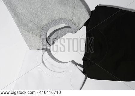 Close Up Shot Of Three Perfectly Folded Monochrome Sweatshirts Gray, Black And White Laid Out In A C
