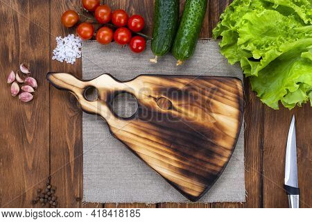 Cutting Wooden Board On A Wooden Table. Handmade Chopping Board. Fresh Tomatoes, Cucumbers And A Cut